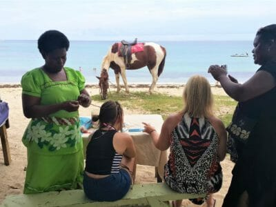 Getting hair braided by Fijian Ladies at Natadola Beach on a day tour in Fiji