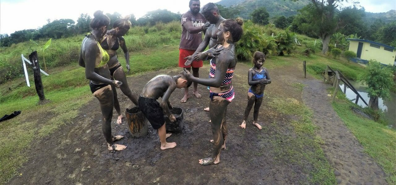 Tour group painting themselves at the local mud pools in Fiji